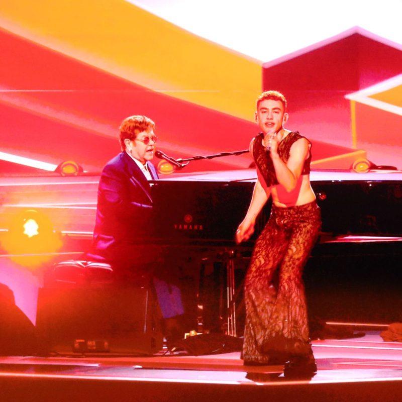 Imagem da apresentação de Elton John e Olly Alexander no BRIT Awards 2021. Mostra Olly, homem branco de cabelos vermelhos curtos, com uma calça estampada preta e uma blusa curta de mesma estampa cantando em pé com um microfone na mão. Atrás dele está John, homem branco de cabelos castanhos curtos e terno azul marinho, sentado em um piano preto com um microfone à sua frente.