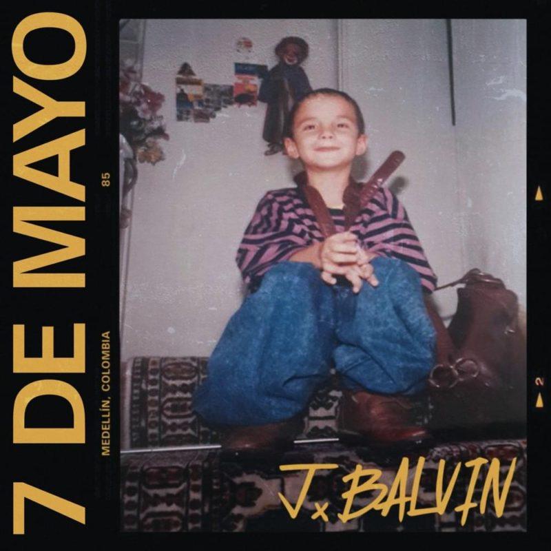 Capa do single 7 de Mayo, de J Balvin. A capa é composta por uma fotografia do artista enquanto criança. Ele, por volta de nove anos, está sentado num sofá com estampa étnica, na fentre de uma parede branca com enfeites pendurados. O menino sorri levemente e olha para a frente, vestindo uma camiseta com listras rosas e azuis, uma calça jeans e botas marrons. Ele segura uma mochila de couro marrom, encostada ao seu lado direito, e ao redor do seu pescoço, existe um cinto de couro marrom. No canto inferior direito da imagem, está a assinatura de J Balvin, numa fonte desenhada em caixa alta colorida em amarelo. No canto esquerdo da imagem, existe uma faixa preta que cria um fundo para um escrito do nome da música, em caixa alta e amarelo. Embaixo do nome e cercando toda a fotografia, existe um quadro preto que imita um filme de câmera antiga. Nesse quadro, na parte de cima, que está embaixo do nome da música, na vertical, está escrito Medellín, Colombia. Na parte de baixo do quadro, que está no canto esquerdo da imagem, existe o símbolo de 'play'.