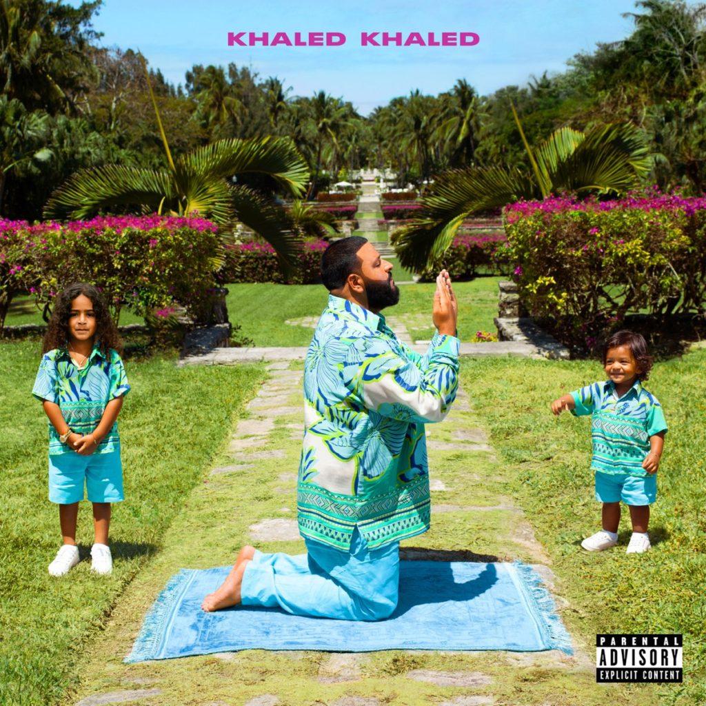 Capa do álbum KHALED KHALED, de DJ Khaled. A capa é uma fotografia do artista num jardim ao lado dos seus dois filhos. Khaled está ao centro, ajoelhado para o lado direito em cima de um tapete azul, com as mãos em sinal de prece. Ele, um homem arábe de cabelos castanhos raspados e barba, veste um terno azul. Ele está no que parece ser um caminho do jardim, enquanto seus dois filhos estão um de cada lado dele na grama. As crianças aparentam ter entre três e seis anos e também vestem roupas azuis. Ao fundo, pode-se observar um jardim grandioso e podado com flores rosas surgindo dos arbustos. A parte superior da capa mostra um pedacinho de céu azul, onde está escrito o nome do disco numa fonte em tom de rosa, caixa alta e negrito.