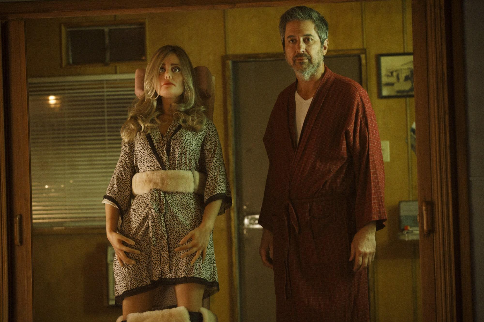 Cena da série Made For Love. No centro da foto está Herbert, interpretado pelo ator Ray Romano. Ele é um homem branco, de barba e cabelo grisalho. Ele veste um roupão vinho. Ao seu lado está uma boneca em tamanho real, ela é loira de olhos azuis, usa um robe estampado e se chama Diane.