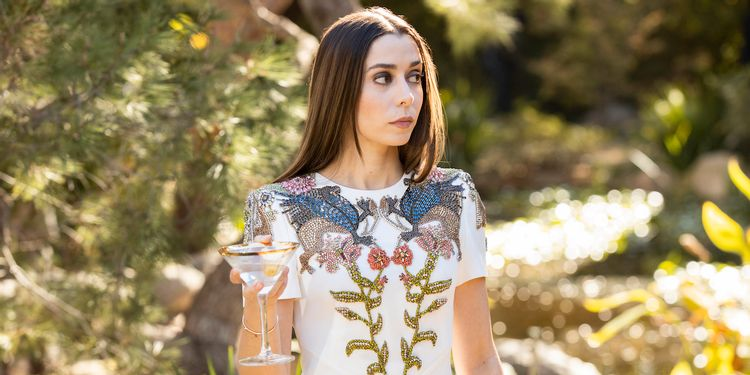 Cena da série Made for Love. Nela, vemos Cristin Milioti segurando uma taça de martini. Ela é branca, tem cabelos castanhos e veste um vestido branco, com detalhes florais em azul e verde. Está de dia e atrás dela vemos folhagens verdes.