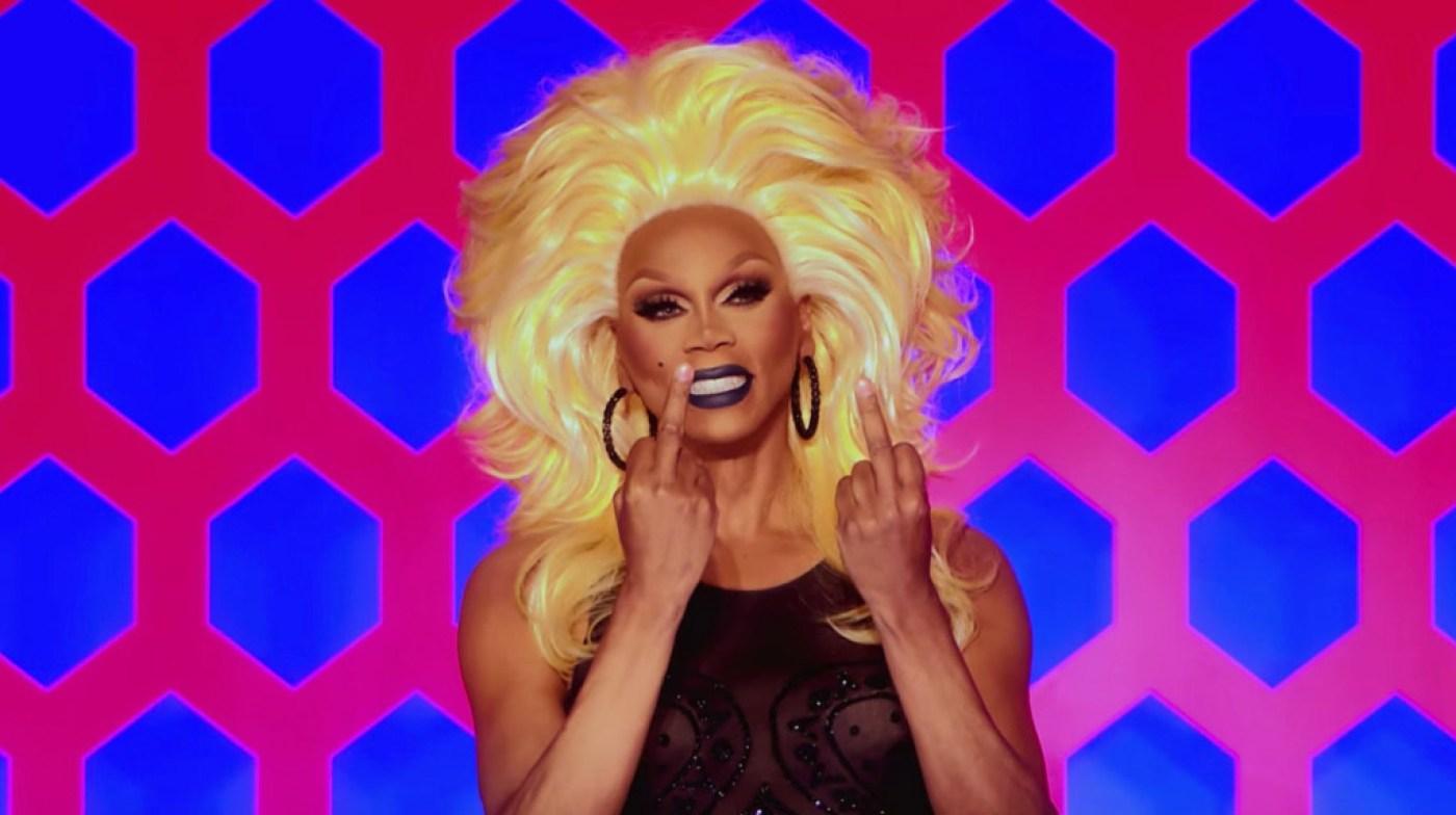 Cena da 13ª temporada do reality show RuPaul's Drag Race. Nela, vemos RuPaul, de peruca loira e vestido preto, sorrindo enquanto levanta seus dois dedos do meio em direção à Utica.