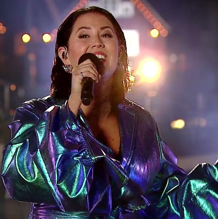 Foto de Molly Sandén cantando no Oscar 2021. Ela é branca, de cabelos pretos e veste um vestido com mangas bufantes azul brilhoso.