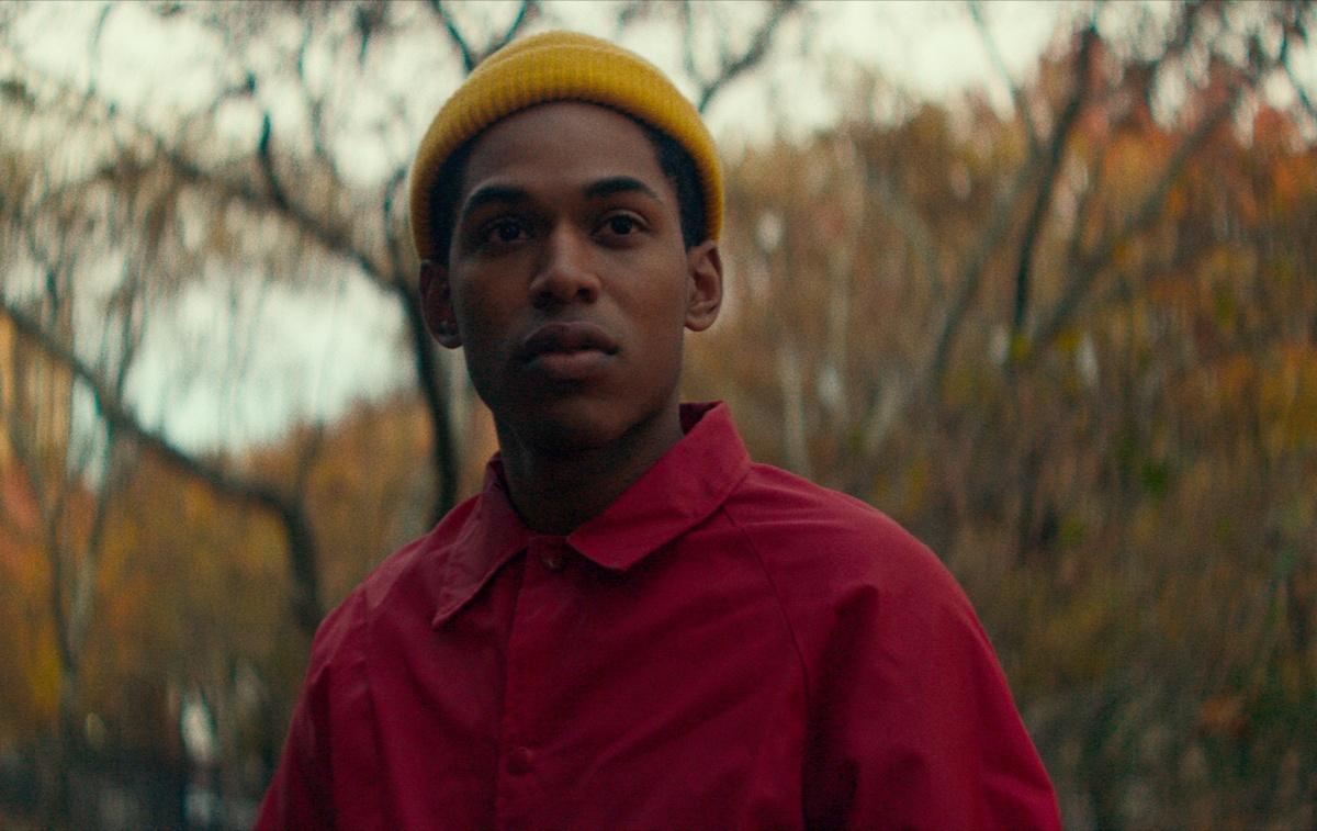 Foto de uma cena do filme Monstro. A imagem monstra um jovem negro e magro olhando para frente com uma expressão séria. Ele veste uma camisa vermelha e uma touca amarela, que cobre seu cabelo curto. No fundo é possível ver árvores com folhas alaranjadas e um céu cinzento.