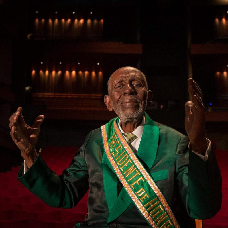 Foto de Nelson Sargento. Nelson é um homem negro de 96 anos, careca com a barba rala branca. Ele está sentado, usa paletó verde e uma faixa escrita PRESIDENTE DE HONRA. Seus braços estão abertos.