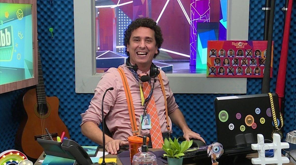 Cena do Big Brother Brasil 21. A imagem mostra Rafael Portugal sentado em sua mesa do quado CAT BBB.