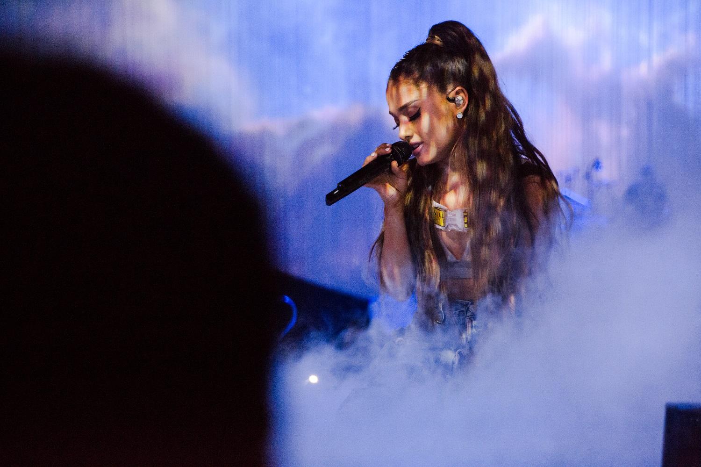 Foto da turnê Dangerous Woman. Ariana está sentada, e uma fumaça cobre parte de suas pernas. Ariana é uma mulher branca, seus cabelos são castanhos e estão presos em um rabo de cavalo pela metade. Ela veste um cropped branco e dourado e segura um microfone. Sua expressão é serena e seus olhos estão fechados.