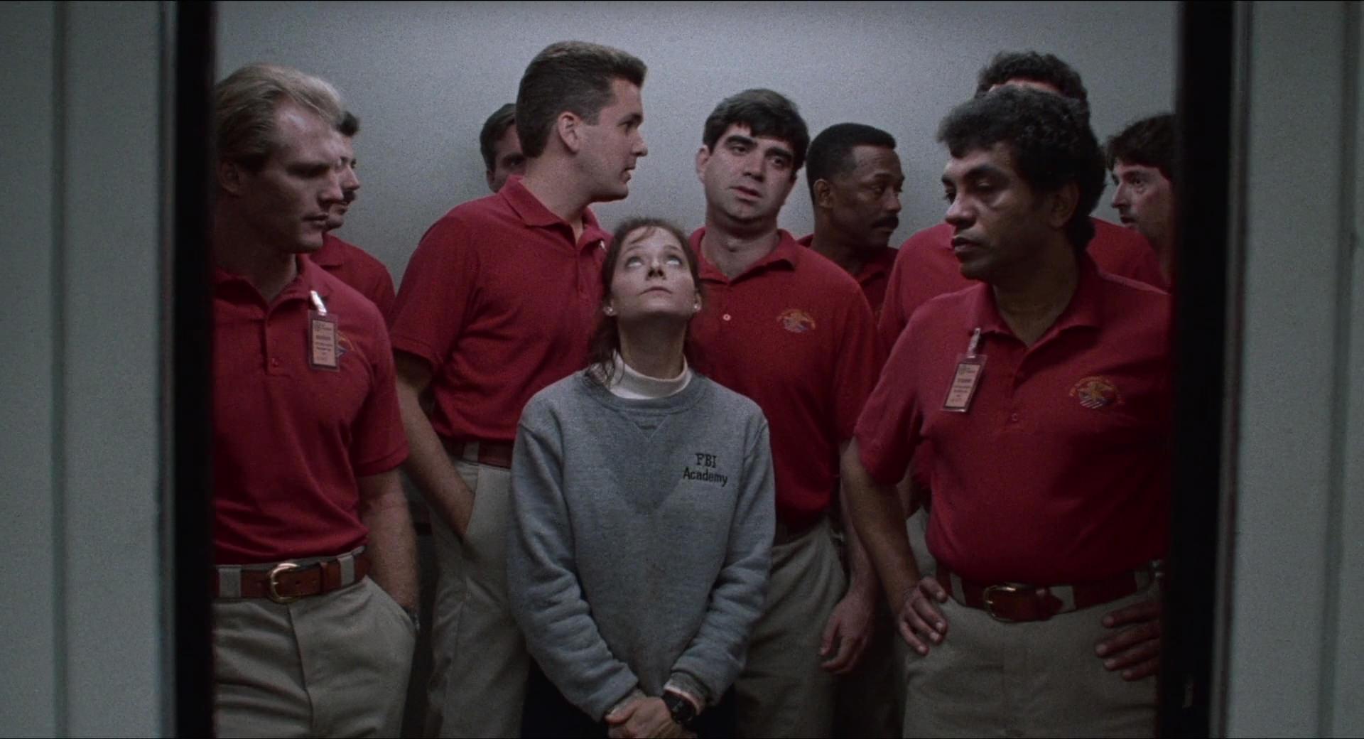 Cena do filme O Silêncio dos Inocentes. Jodie Foster está no centro da imagem, dentro de um elevador. Ela usa moletom cinza com uma camisa branca por baixo marcados com suor, calças pretas e suas mãos estão unidas na frente do corpo. Ao redor dela, vamos nove homens no pequeno espaço. Todos usam a mesma roupa: camisa polo vermelha e calça cáqui bege.