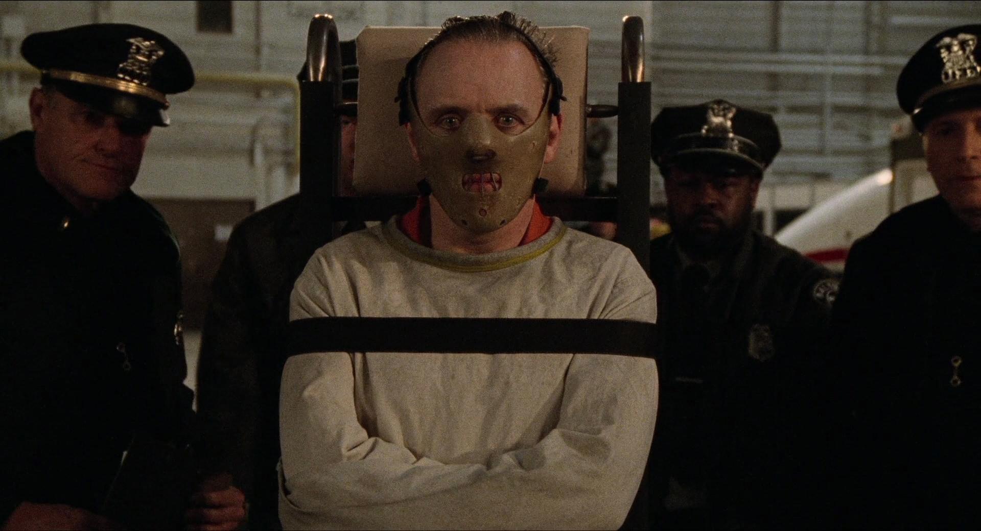 Cena do filme O Silêncio dos Inocentes. O personagem de Anthony Hopkins está no centro da imagem, preso em uma camisa de força. Ele está de pé, num carrinho, e usa uma máscada de couro do nariz para baixo. Seu olhar é vidrado, sem expressões. Ao seu redor, vemos três policiais desfocados.
