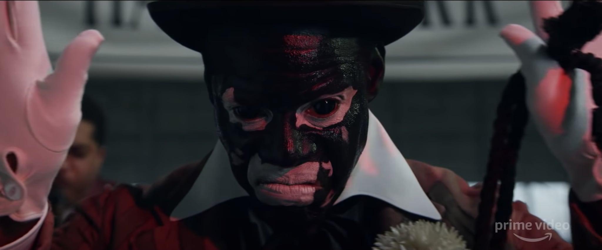 Cena da série Them. Nela, vemos um homem com o corpo pintado de preto, cor de piche, mas com os olhos e a boca contornados de branco. Ele usa chapéu preto e luvas brancas, tem as mãos levantadas e segura um objeto como uma bengala preta na mão esquerda.