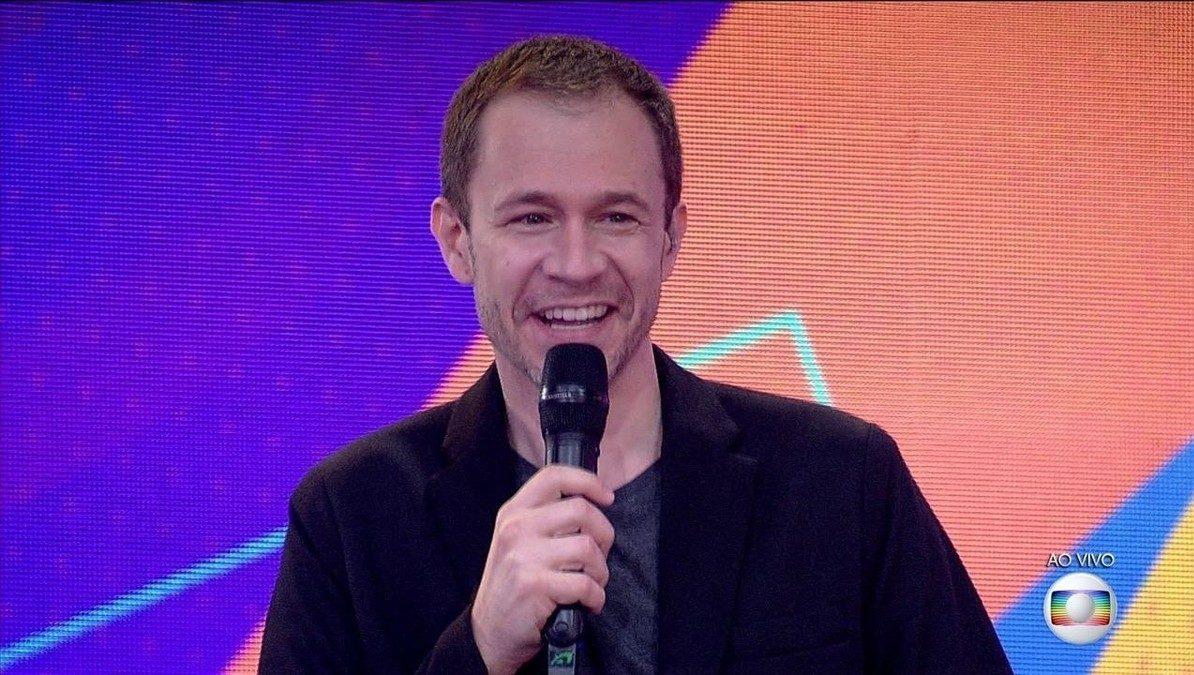 Cena do Big Brother Brasil 21. O apresentador Tiago Leifert sorri enquanto segura o microfone.