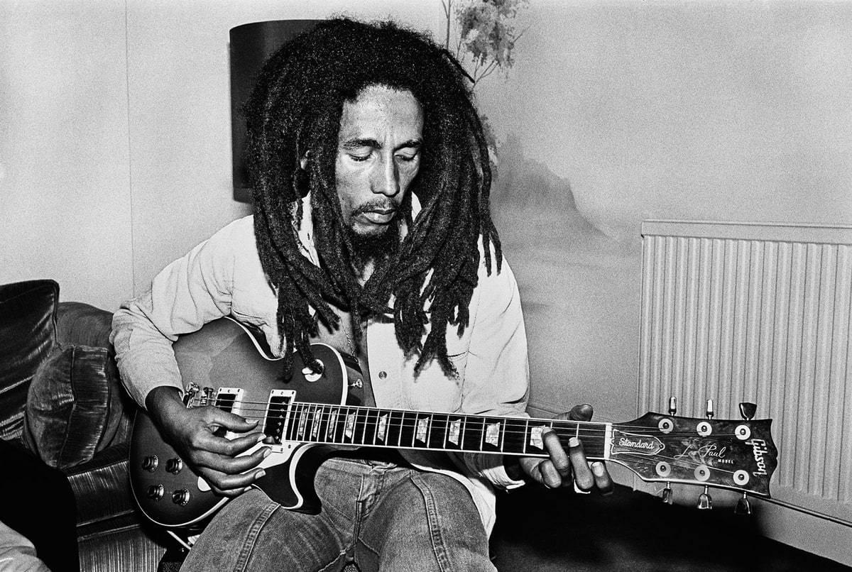 A imagem retangular está em preto e branco. Ao centro vemos Robert Nesta Marley, um homem negro, de dreadlocks longos na altura do ombro e barba rala e rústica. Ele possui um rosto magro e olha para baixo, enquanto está sentado ele usa uma camiseta de manga longa aberta branca e uma calça jeans. Sobre seu colo ele dedilha uma guitarra modelo Gibson. Ao fundo podemos ver um sofá escuro à esquerda e uma parede branca.