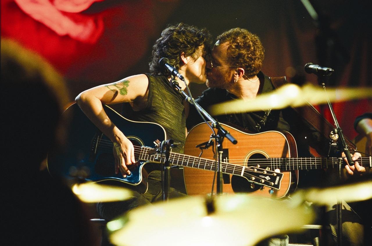 Foto de Cássia Eller e Nando Reis. Nando é um homem branco de cabelo ruivo e curto. Ele veste camisa preta. Ambos estão sentados e seguram seus respectivos violões. Eles estão se beijando. O fundo tem luzes vermelhas.
