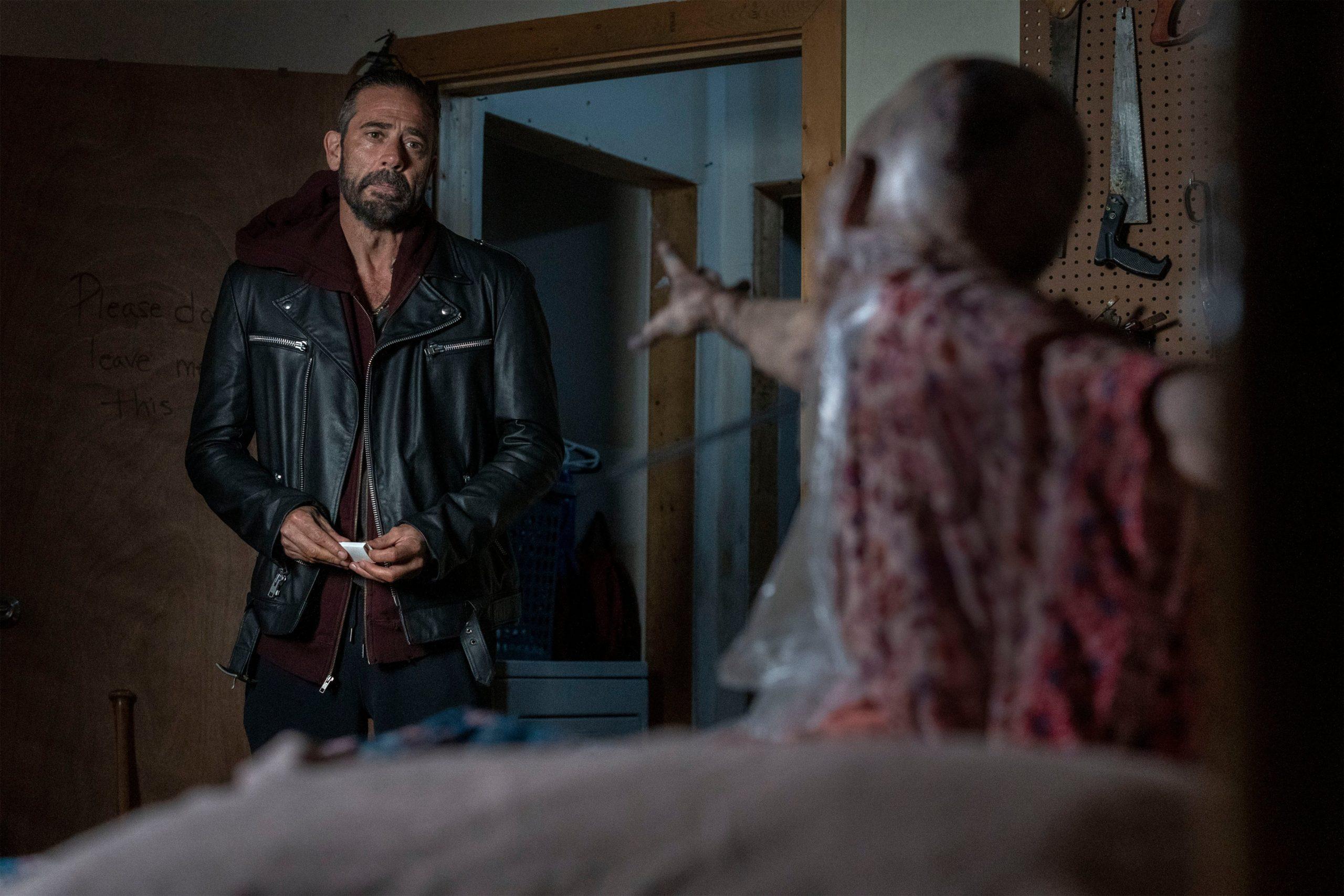 Cena de The Walking Dead. Nela, vemos Negan, papel de Jeffrey Dean Morgan, parado à porta, vendo sua esposa zumbificada presa à cama. Ele é branco, tem barba, usa jaqueta de couro. Ela é careca e está esticando a mão em direção a ele.