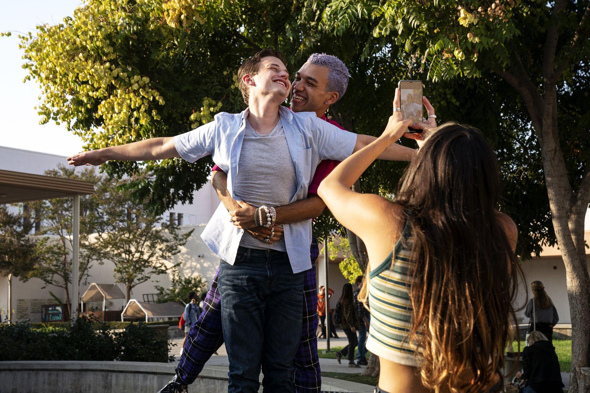 Cena de Genera+ion. Chester, um jovem negro de pele clara, abraça por trás Nathan, um jovem branco. Eles estão imitando a famosa pose de Titanic. Na frente deles, uma menina está tirando foto dos dois usando um celular. Eles estão em cima de uma muretinha, no pátio de uma escola.