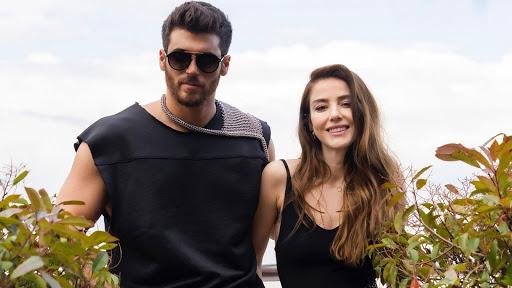 Foto da novela Bay Yanlis. Na imagem estão os personagens Özgür e Ezgi, Ezgi é vivida por Özge Gürel, é uma mulher branca de cabelos castanhos compridos e olhos castanhos, ela veste uma blusa preta de alças e está sorrindo. Özgür é um homem branco de cabelos e olhos castanhos, ele veste uma regata preta e usa óculos escuros, e é interpretado pelo ator Can Yaman. Ambos estão com os braços juntos por trás. O cenário de fundo está desfocado.