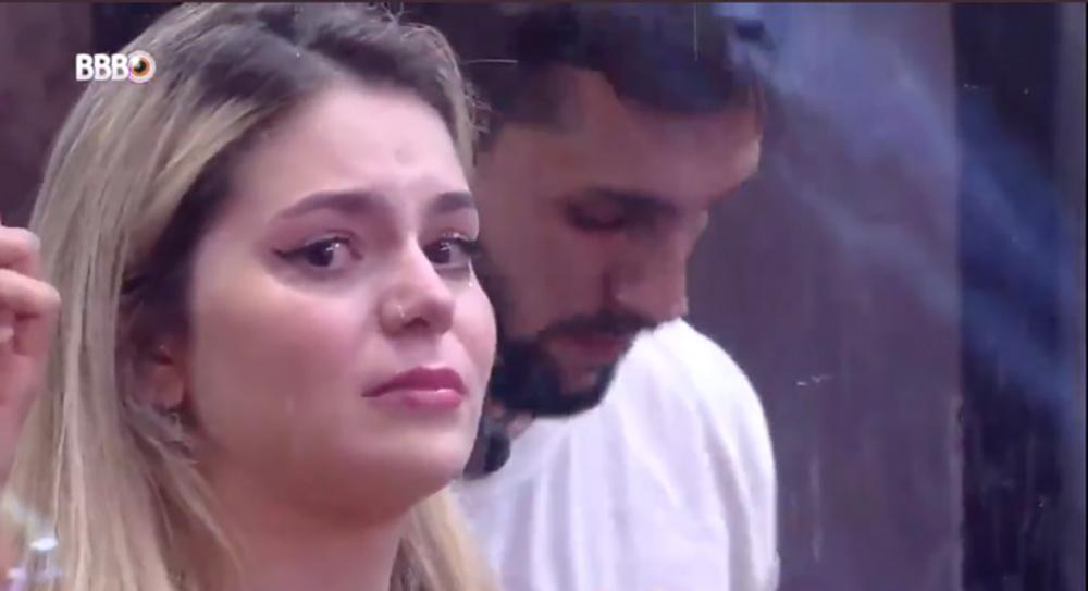 Cena do Big Brother Brasil 21. Viih Tube olha diretamente para a câmera com rosto emocionado. Ao fundo, podemos ver Arthur desfocado.