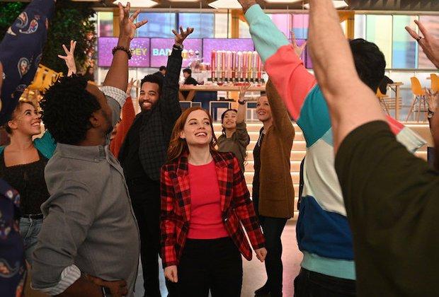 Cena da série Zoey e sua Fantástica Playlist. Na cena vemos Zoey em um número musical com seus colegas de trabalho. Zoey é uma mulher branca, de cabelos ruivos com um blazer vermelho. Seus colegas de trabalho estão dançando e a maioria está usando roupas sociais.