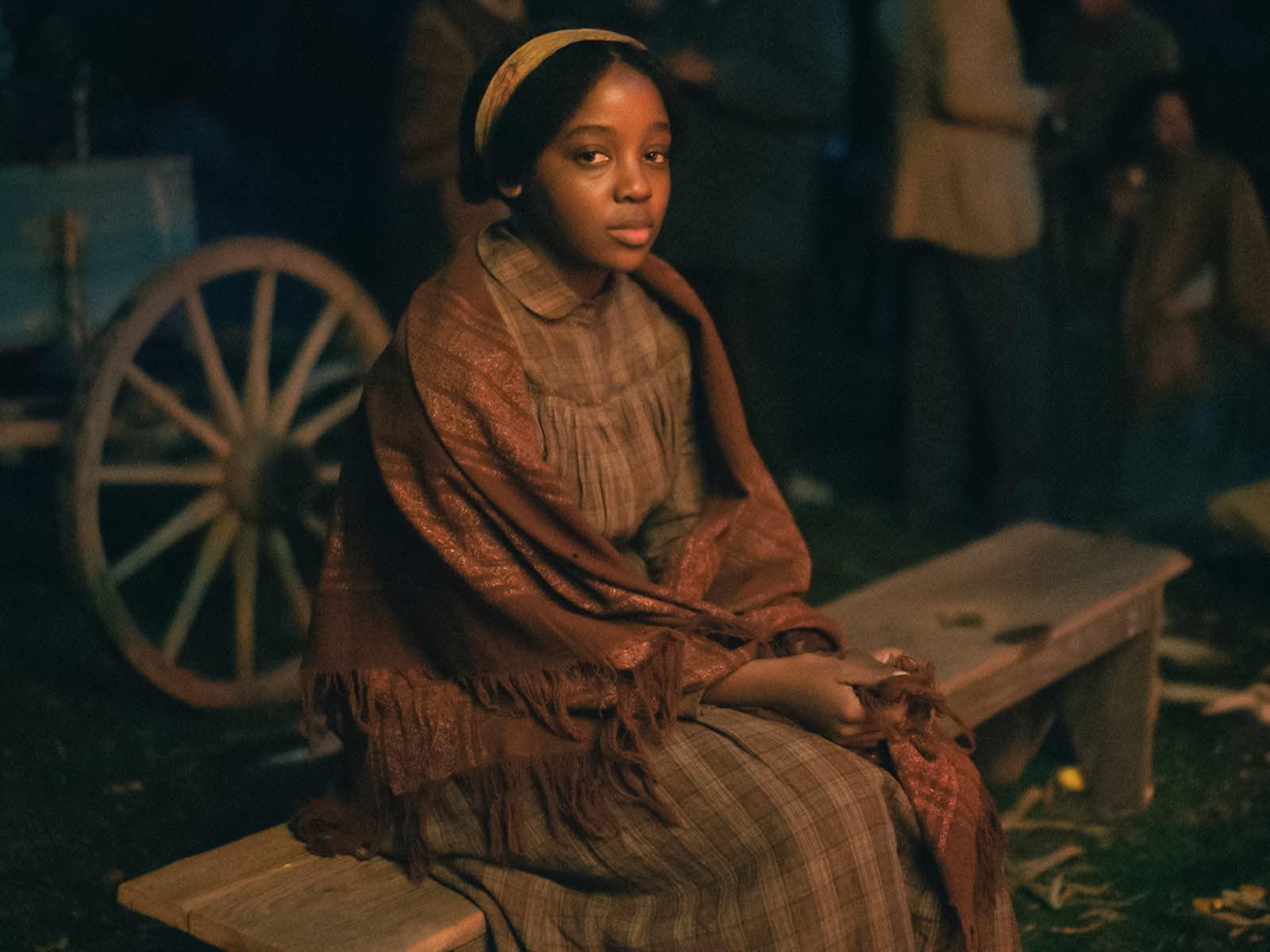 Cena de The Underground Railroad: Os Caminhos Para a Liberdade. A imagem mostra Cora, personagem de Thuso Mbedu, uma jovem negra de cabelos crespos e olhos redondos. A imagem é de uma cena noturna, onde Cora é fotografada quase de corpo inteiro, sentada num banco de madeira, levemente inclinada para a esquerda. Cora encara a câmera com neutralidade na expressão. Cora usa um vestido longo de estampa xadrez marrom e um xale com estampa de xadrez vermelho amarronzado. Cora também usa uma tiara amarela e seus cabelos estão presos para trás. Cora segura as pontas do xale em cima do colo com firmeza. Atrás de cora, levemente desfocado, pode-se observar as rodas e parte de uma carroça azul e outras pessoas de pé bebendo. O rosto de Cora reflete uma luz alaranjada, de fogo, e no chão de grama verde, existem folhas secas.