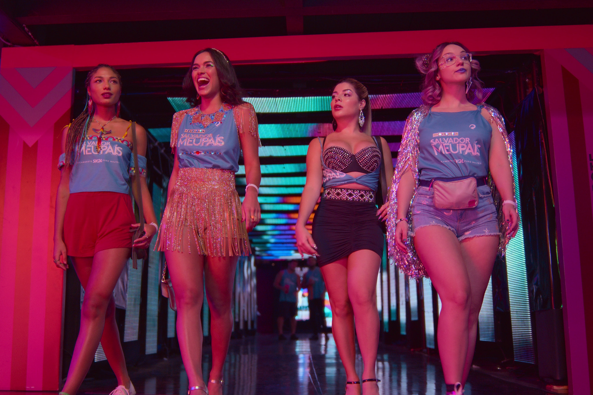 Na foto, 4 mulheres caminham em um corredor iluminado azul e rosa. Da direita para a esquerda, uma mulher branca, de cabelos rosas, usa uma blusa azul com mangas de brilho, um shorts jeans e uma pochete dourada, a segunda, mulher branca, usa um top com brilhos pratas e detalhes em azul, usa uma saia preta com um cinto prateado; está com os cabelos loiros presos em um rabo. A terceira, uma mulher negra, de cabelos pretos, usa uma blusa azul com detalhes em dourado, e uma saia dourada. A última, mulher negra, usa tranças nos cabelos pretos, uma blusa azul com um shorts vermelho