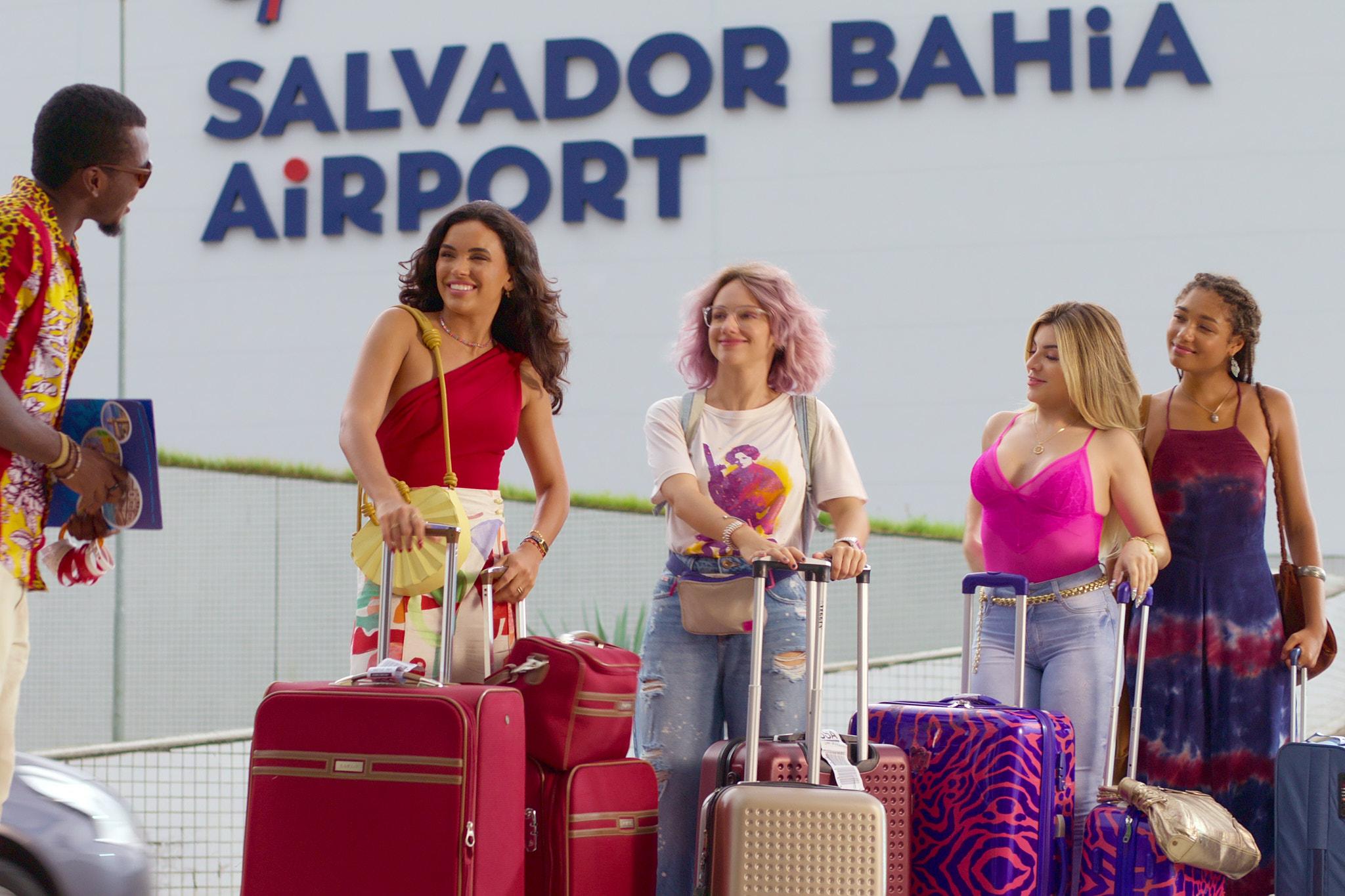 Imagem do filme Carnaval. Na imagem, ao fundo podemos ver o letreiro do aeroporto de Salvador com o escrito SALVADOR BAHIA AIRPORT. Da direita para a esquerda, temos uma mulher negra, de cabelos com tranças, usando um vestido vinho e azul, segurando uma bolsa marrom no ombro, e uma mala de viagem azul. A seu lado, uma mulher branca, de cabelos loiros, usa uma blusa de alça rosa, com um calça jeans, segurando uma mala de viagem azul e rosa nas mãos, com uma igual à sua frente. Depois, uma mulher branca, de cabelos rosas, usa uma blusa estampada branca, com calças jeans, está com uma mochila e uma pochete em seu corpo e segura com as mãos malas douradas e rose. A última, uma mulher negra, de cabelos pretos, usa uma blusa de uma manga vermelha e uma saia estampada bege, segurando uma bolsa amarela e malas vermelhas. No canto esquerdo, ainda podemos ver um homem negro, usando um acamisa amarela e vermelha estampada e segunda uma pasta azul.