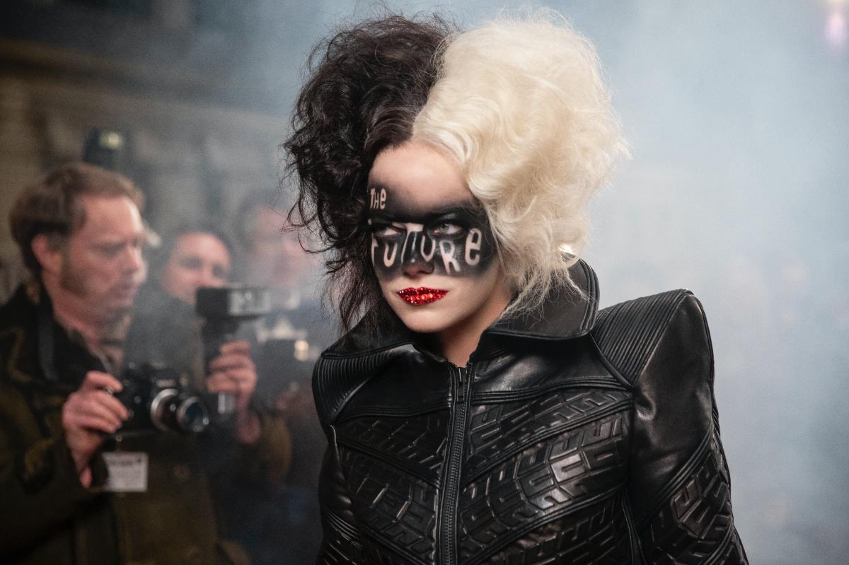"""Foto retangular de uma cena de Cruella. A atriz Emma Stone está no centro, do peito para cima, como Cruella. Ela é branca, possui olhos azuis claros e cabelos presos para cima, metade branco (lado esquerdo dela) e metade preto (lado direito dela). Ela possui uma maquiagem preta sobre o rosto como fundo e os escritos """"THE FUTURE"""" e um batom vermelho brilhante. Ela veste uma jaqueta preta de couro, com gola. O fundo está um pouco desfocado, mas do lado esquerdo de Emma se vê vários fotógrafos segurando câmeras antigas pretas. O lado direito de Emma está com uma fumaça branca."""