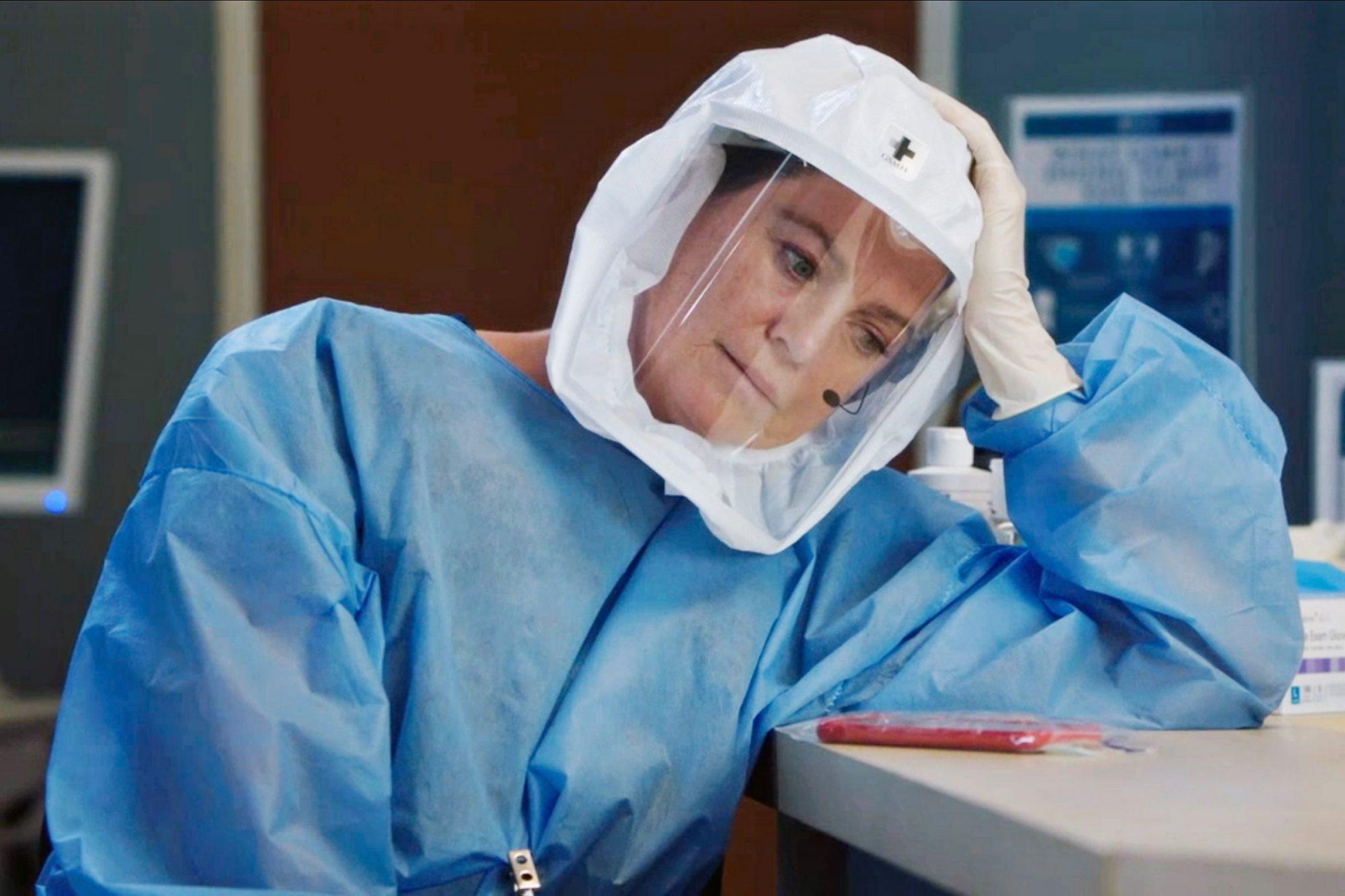 Imagem da série Grey's Anatomy. Na imagem, uma mulher branca usando um jaleco de médico azul, luvas e uma espécie de capacete branco e com o visor na frente transparente. Ela apoia a cabeça em uma mesa branca, em que está apoiado seu celular vermelho embalado em um plástico. Ao fundo, é possível ver uma porta marrom e um quadro azul escuro na parede.