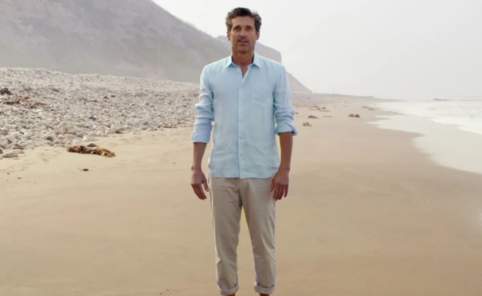 Imagem da série Grey's Anatomy. Na imagem, um homem branco de cabelos pretos usa uma camisa azul clara e calças de sarja bege clara. Ele está em uma praia, que podemos ver ao fundo do lado direito parte do mar e do lado esquerdo pedras que preenchem sua extensão, assim como a areia clara.