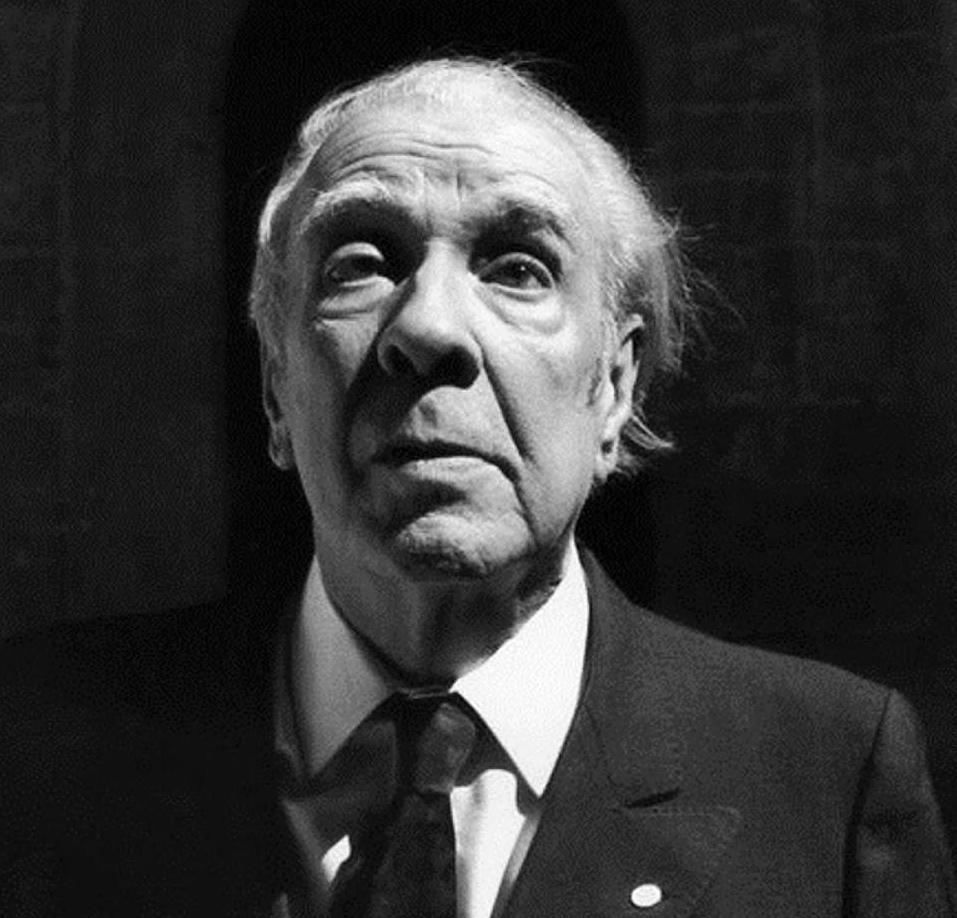 Foto em preto e branco do escritor Jorge Luis Borges. Ele é um homem caucasiano, de cabelos brancos, veste terno preto, camisa branca e gravata preta. Ele mantém a cabeça ereta, enquanto olha para a frente