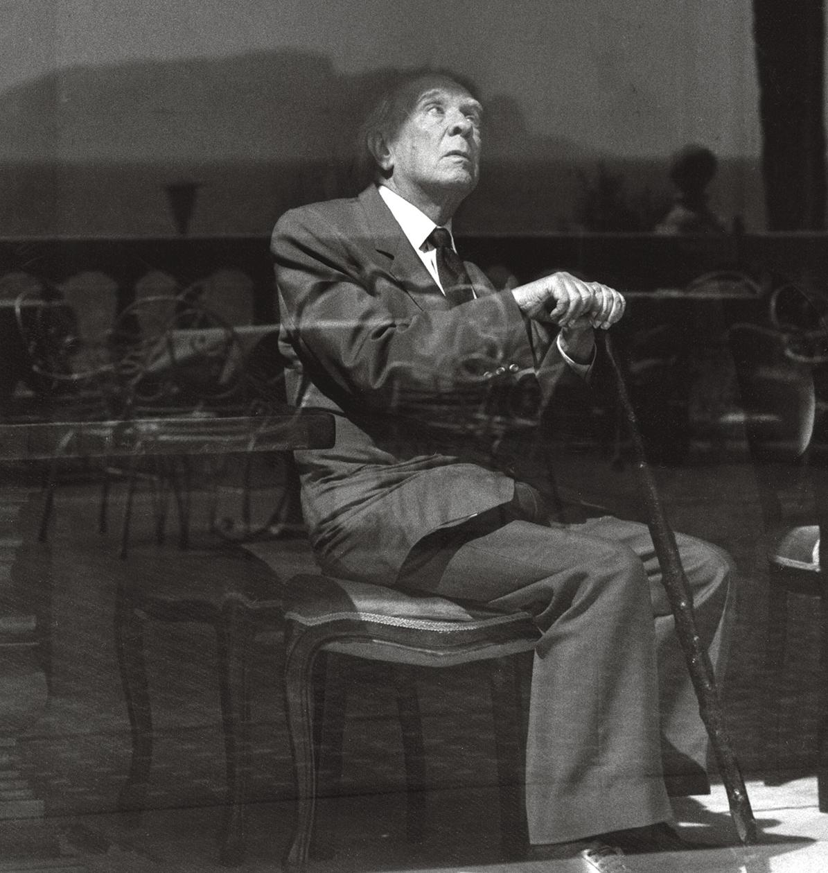 Foto em preto e branco do escritor Jorge Luis Borges. Ele é um homem de cabelos brancos, veste terno e gravata, e está sentado em uma cadeira enquanto segura uma bengala. Está com a cabeça inclinada para trás, olhando para cima