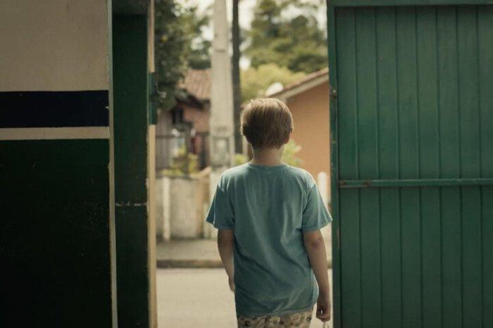 Cena da série documental O Caso Evandro. A imagem mostra um portão verde de madeira aberto, ao lado de uma parede pintada metade branca e metade verde, com uma faixa azul. Saindo pela porta está um menino branco, loiro, de costas, com um short estampado e uma camisa azul clara, segurando um molho de chaves. À sua frente está uma rua, com uma casa alaranjada e um muro baixo branco, notam-se algumas árvores ao fundo desta casa.