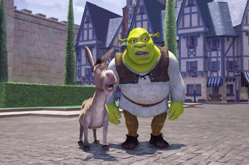 Cena do primeiro filme da franquia de Shrek. A imagem mostra dois personagens principais da trama: Shrek e Burro. Eles estão em uma vila com casas medievais com ornamentos azuis. Ambos estão ao centro da imagem e estão boquiabertos (surpresos). Shrek é um ogro careca, barrigudo e verde. Ele está vestindo camisa de manga longa branca, calça marrom e sapatos pretos. Ao lado esquerdo de Shrek, Burro é um animal quadrúpide cinza que não veste nenhum acessório.