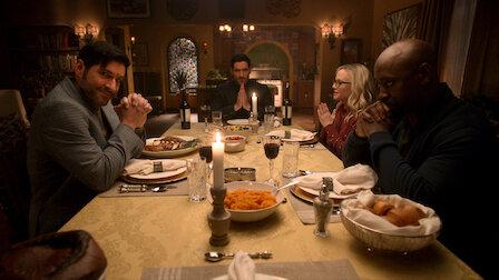 A imagem é uma foto. A esquerda encontra-se Miguel, sentado em uma mesa de madeira posta com comidas, pratos, talheres, taças de vinhos e velas. Ele está com os cotovelos apoiados na mesa e as mãos entrelaçadas. Depois dele, à ponta da mesa, senta Lúcifer com as mãos em posição de reza. Logo depois dele, à direita da imagem e do outro lado da mesa, está Linda. Ela é uma mulher branca de cabelos loiros que usa óculos preto, e também está com as mãos em posição de reza. Por fim, ao lado de Linda, sentado na frente de Miguel, está Amenidieal. Ele é um homem negro, careca e que tem um cavanhaque ralo, e está com as mãos cruzadas apoiadas no queixo.