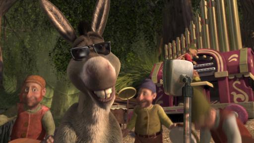 A imagem simboliza a cena final de celebração do casamento de Shrek e Fiona no pântano. Burro está cantando em um microfone e usa óculos escuros. Ao fundo estão presentes os anões da Branca de Neve tocando instrumentos musicais.