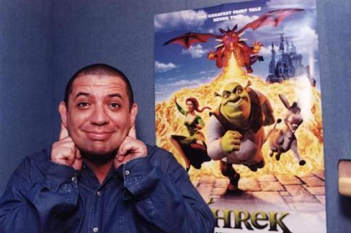 A imagem exibe o ator e comediante Bussunda fazendo um gesto similar às orelhas do ogro Shrek. Bussunda é um homem gordo, branco e careca. Ele veste uma jaqueta jeans azul e está na frente do cartaz oficial do filme que mostra Shrek, Fiona e Burro fugindo do Dragão que cospe fogo.