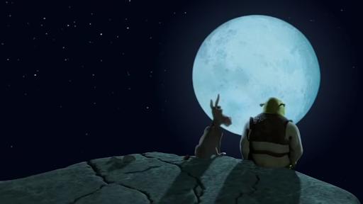 Cena do filme em que Shrek e Burro aparecem sentados na beira de um penhasco refletindo à luz do luar. Ambos estão sentados admirando a lua. Sherek está com sua roupa convencional: camisa longa branca, colete e calças marrons e sapatos pretos. Burro não veste roupa. Shrek está cabisbaixo.