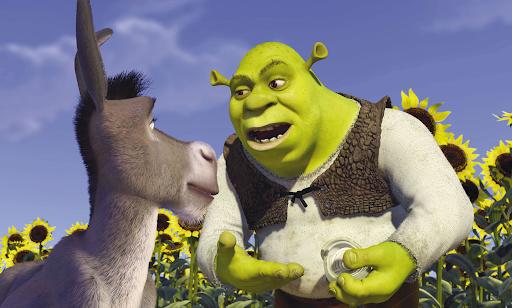 Shrek e Burro em uma cena que ambos estão conversando ao redor de uma plantação de girassóis. Shrek está com uma cebola na mão.