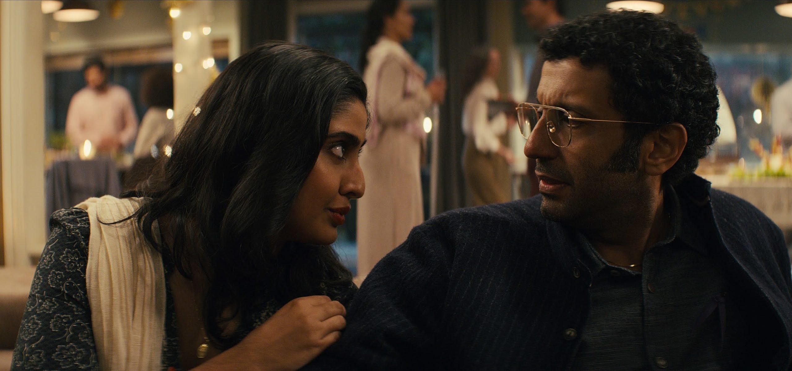 Cena da série Sweet Tooth. Nessa imagem temos o casal Singh, de ascendência indiana, da direita para a esquerda: Rani e Aditya. Ambos em plano conjunto fechado. Eles estão em uma festa na casa de um vizinho, fora de foco há uma casa com luzes amarelas com várias pessoas com roupas mais clássicas em tons sóbrios. Rani tem o cabelo médio, preto e está levemente ondulado ela está sentada de frente e com a cabeça em perfil falando com o marido, olhando nos olhos dele e coloca a mão direita no braço direito dele, ela veste uma blusa preta com estampas simples de folha, em que os elementos têm apenas os contornos e usa um colete bege e um colar com um pingente dourado. Enquanto Aditya está sentado de frente e com o rosto em perfil olhando para a esposa, ele apresenta tensão através do corpo e expressão facial. Ele tem cabelo cacheado e curto, está com a barba aparentando crescer e usa um óculos de grau com armação dourada, ele está vestindo uma camisa cinza escura de botões e uma jaqueta de botões preta com leves listras brancas verticais.