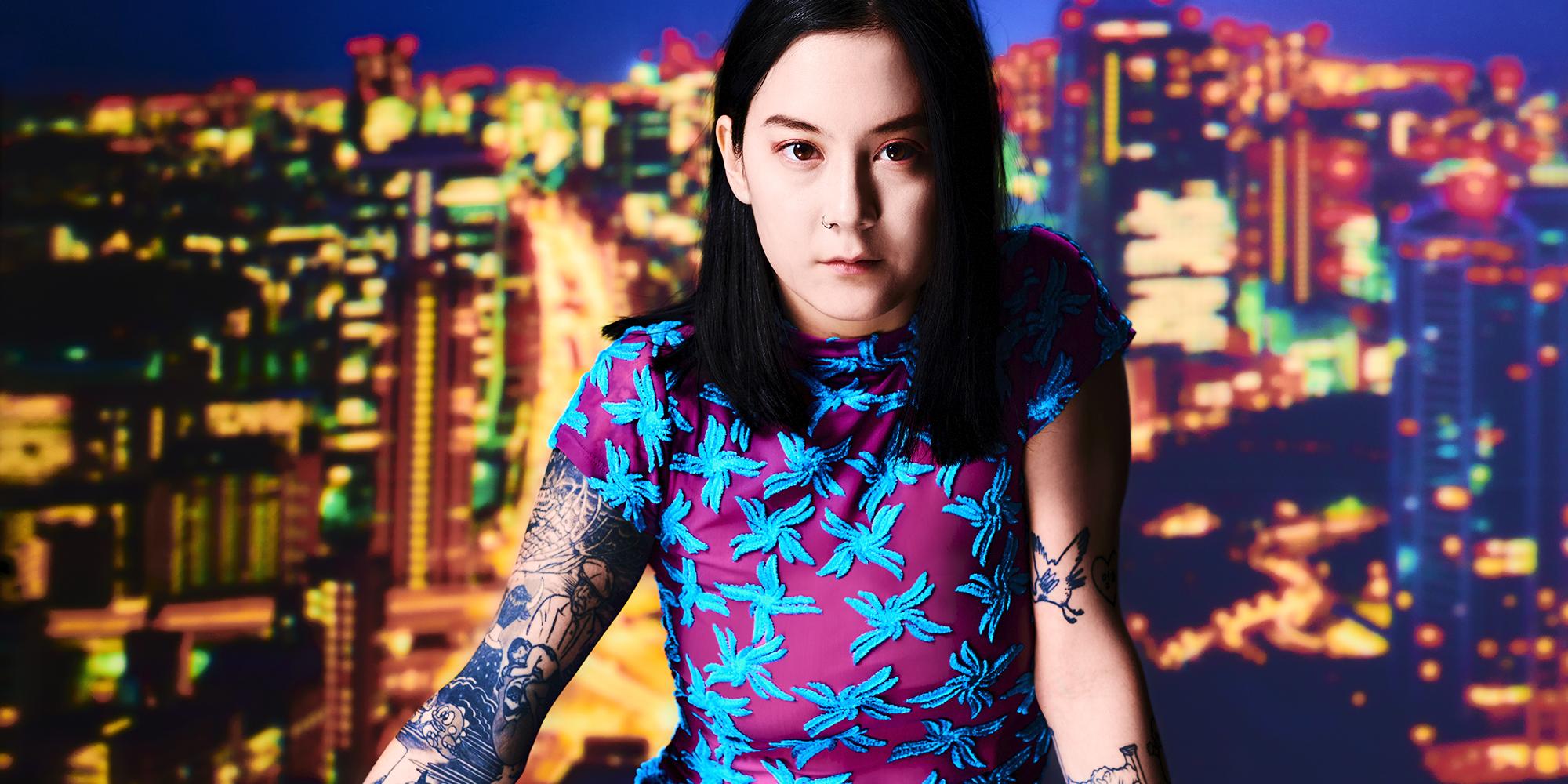 Texto alternativo: Fotografia de Michelle Zauner. A artista está com cabelo solto e um vestido roxo com estampa azul. Ela está na frente de um plano de fundo que imita uma grande cidade à noite, toda iluminada.