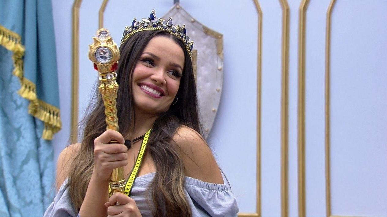 A imagem é uma foto de Juliette durante o Big Brother Brasil 21. Na imagem, ela está dentro do quarto do líder, sorrindo e olhando para o lado direito. Juliette é uma mulher branca, de cabelos castanhos lisos e compridos; ela veste o que parece ser uma blusa azul clara, segura um castiçal dourado na mão e usa uma coroa na cabeça.