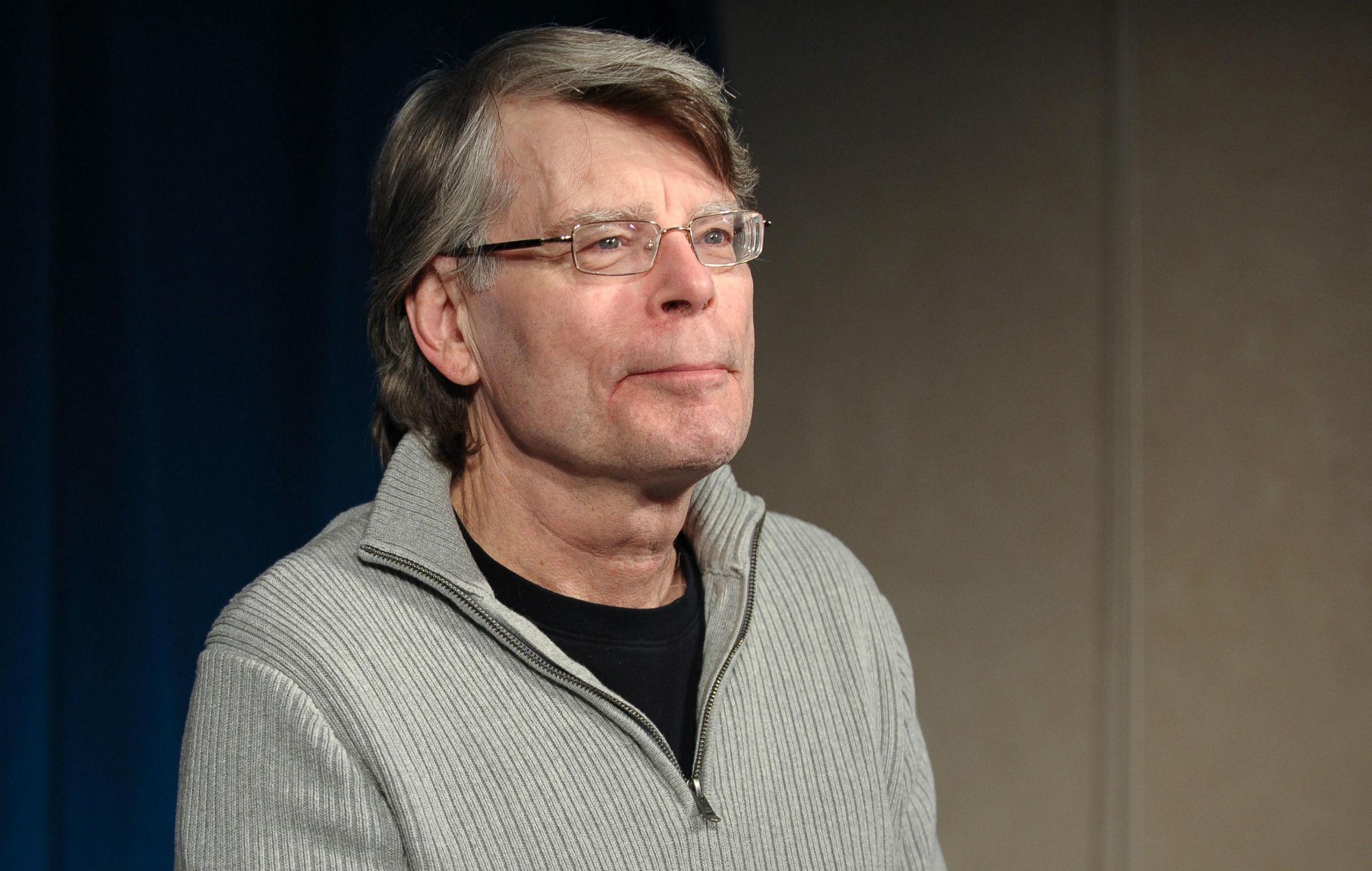 Foto do autor Stephen King. Stephen é um homem branco de 73 anos, com os cabelos levemente grisalhos. Ele usa um moletom cinza com uma camiseta preta por baixo. Possui óculos retangulares.