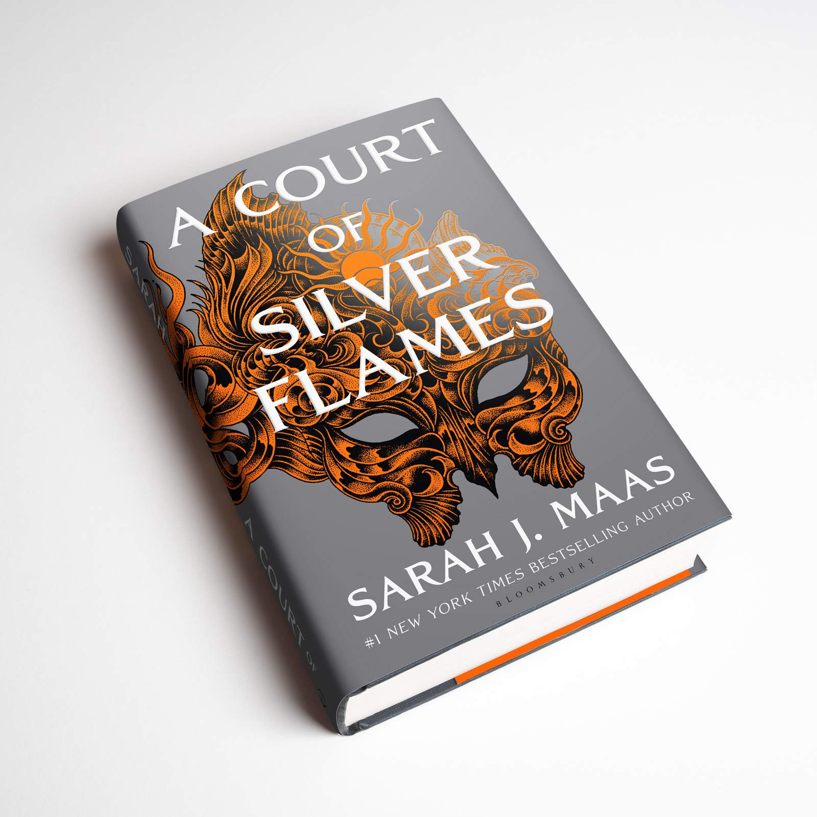 """Foto do livro Corte De Chamas Prateadas, em sua versão original. Em uma superfície branca e lisa, o livro cinza esta apoiado. Na capa há um desenho laranja de uma mascará que segue até a parte de trás. No canto superior até o centro da capa está escrito, em letras brancas, """" A Court Of Silver Flames"""". No canto inferior, também em branco, está o texto 'Sarah J. Maas #1 New York Times bestselling author""""."""
