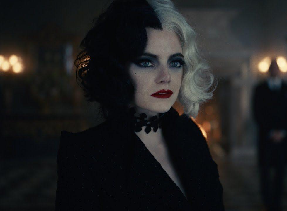 Foto retangular de uma cena de Cruella. A atriz Emma Stone está no centro, dos ombros para cima, como Cruella. Ela é branca de olhos azuis claros e usa maquiagem preta nos olhos e batom vermelho na boca. Ela está com o cabelo curto, ondulado, metade branco (lado esquerdo dela) e metade preto (lado direito dela). Ela veste uma jaqueta preta e uma gargantilha também preta. O fundo está desfocado. No lado esquerdo da imagem, é possível ver cinco luzes redondas amarelas acesas (duas em cima e três embaixo). Atrás de Cruella, se vê uma lareira. No lado direito da imagem, se vê um homem em pé, de terno e gravata, com os braços na frente do corpo. Atrás dele é possível ver duas luzes redondas amarelas acesas.