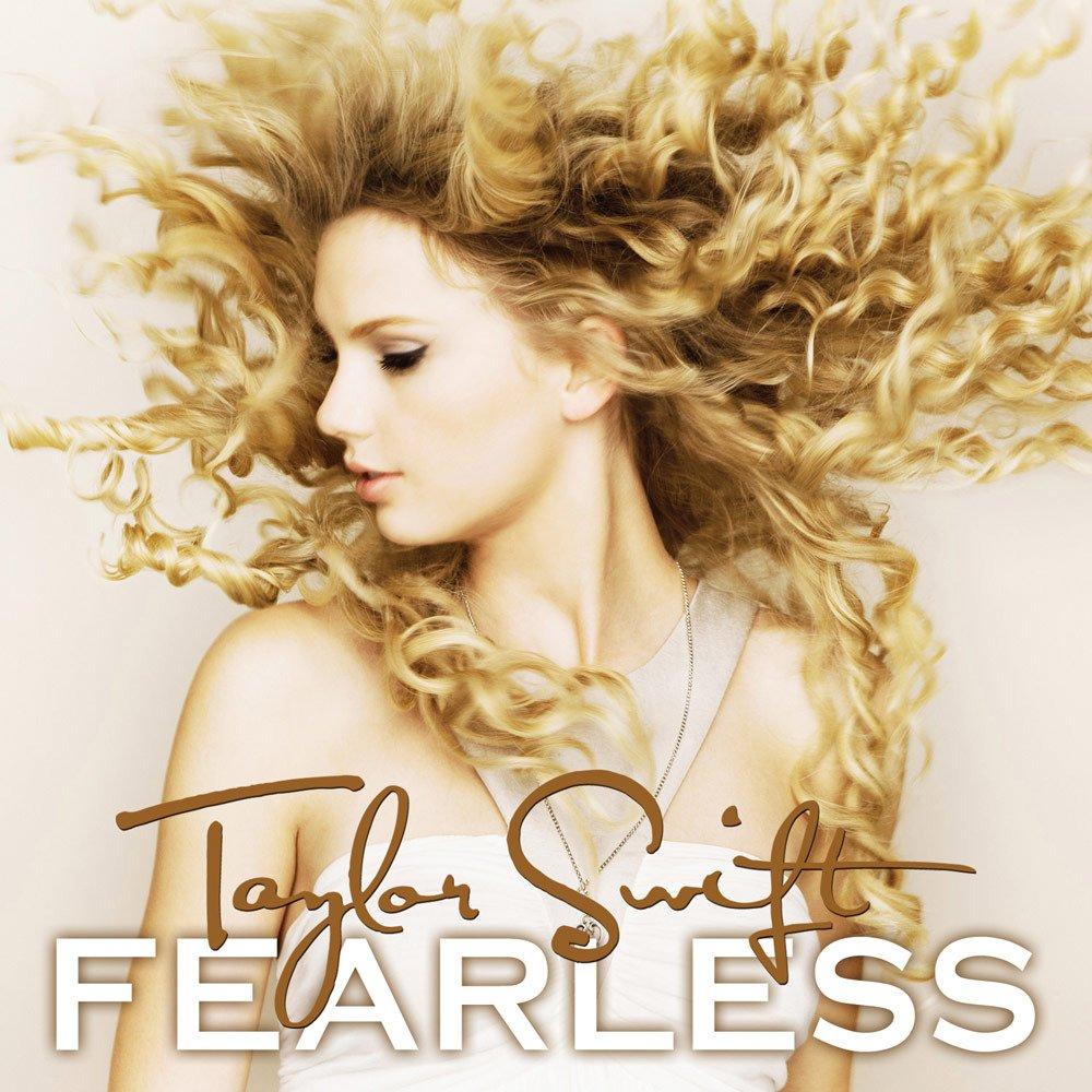 Capa do álbum Fearless, de Taylor Swift. A capa é composta por uma de um fundo branco com Taylor. Ela, uma mulher branca, está ao meio da imagem, com seu cabelo loiro e cacheado jogado para o alto dando a impressão que Taylor estava pulando no momento da foto. Na parte inferior da capa do álbum, ao meio, está escrito o nome de Taylor Swift em letra de mão num tom de marrom claro, e embaixo deste está o nome do álbum, Fearless, em caixa alta e branco com contorno e sombra marrom.