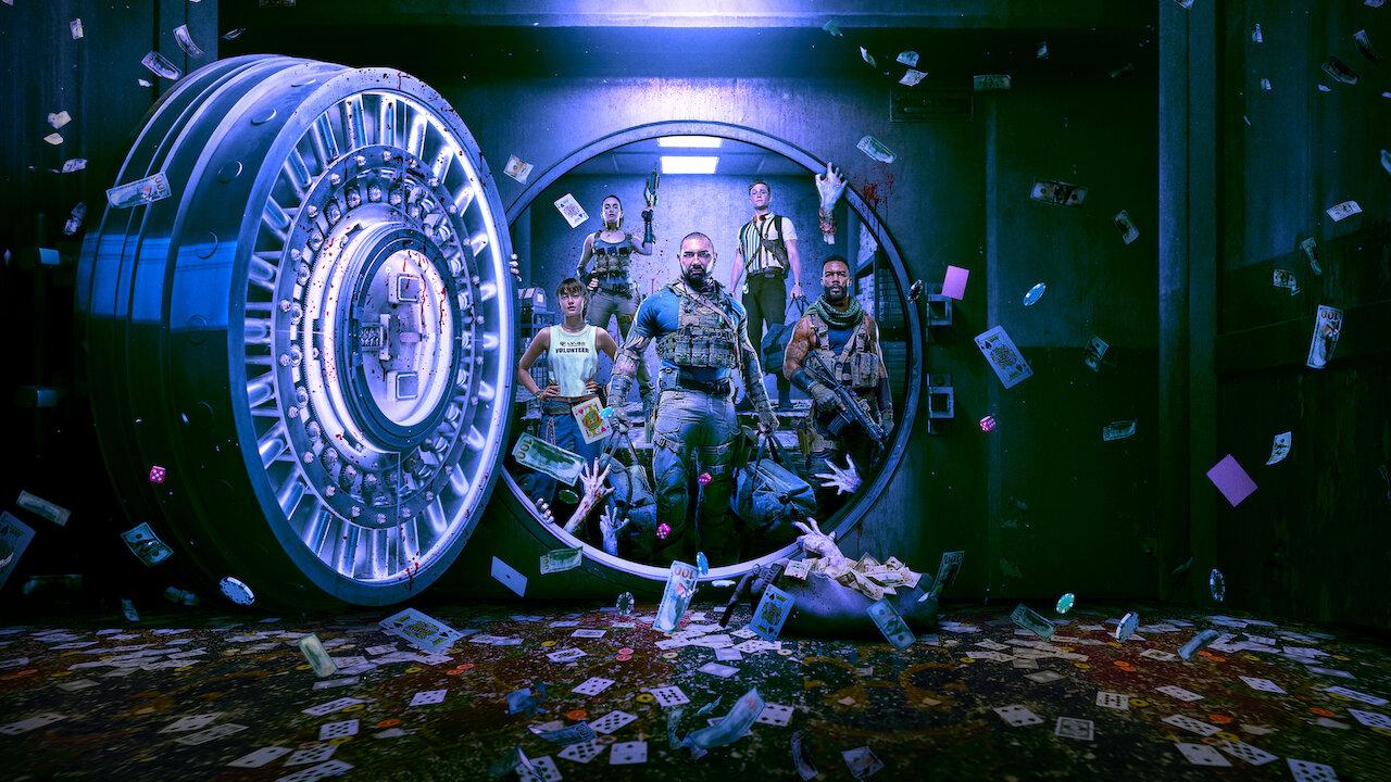 Foto de divulgação de Army of the Dead. Na imagem, ao centro, vemos cinco dos personagens do filme por uma porta de cofre aberta. Eles carregam armas e malas de dinheiro e mãos de zumbis tentam os alcançar. Ao redor da porta, vemos o interior metálico do cofre, onde notas de dinheiro e cartas de baralho voam e há sangue espalhado no chão e escorrendo nas paredes.