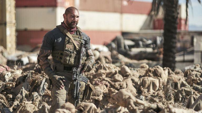 Foto de divulgação de Army of the Dead. Na imagem, vemos o ator Dave Bautista, um homem branco, forte, careca e com uma barba rala castanha, aparentando cerca de quarenta anos, vestindo roupas militares e segurando uma arma. Ele está cercado de esqueletos, espalhados pelo chão.