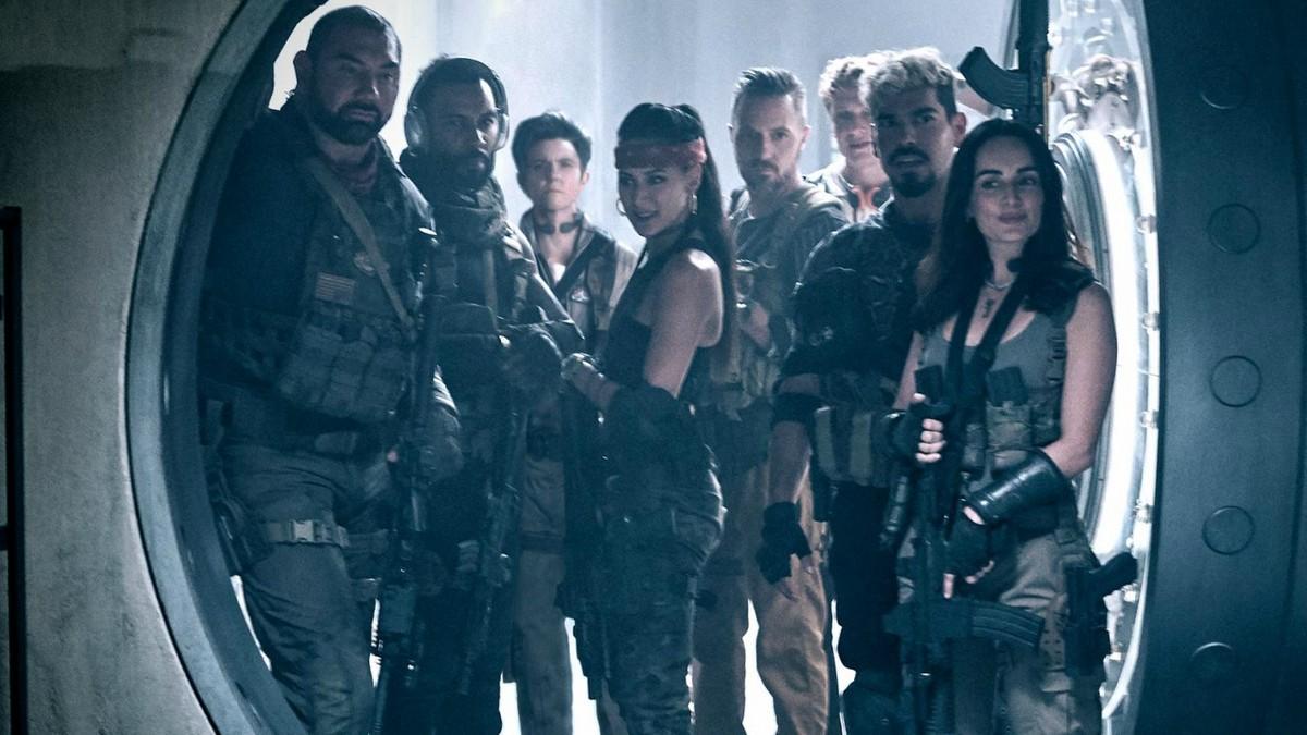 Foto de divulgação de Army of the Dead. Na imagem, ao centro, vemos oito dos personagens do filme armados em frente a uma porta de cofre aberta.
