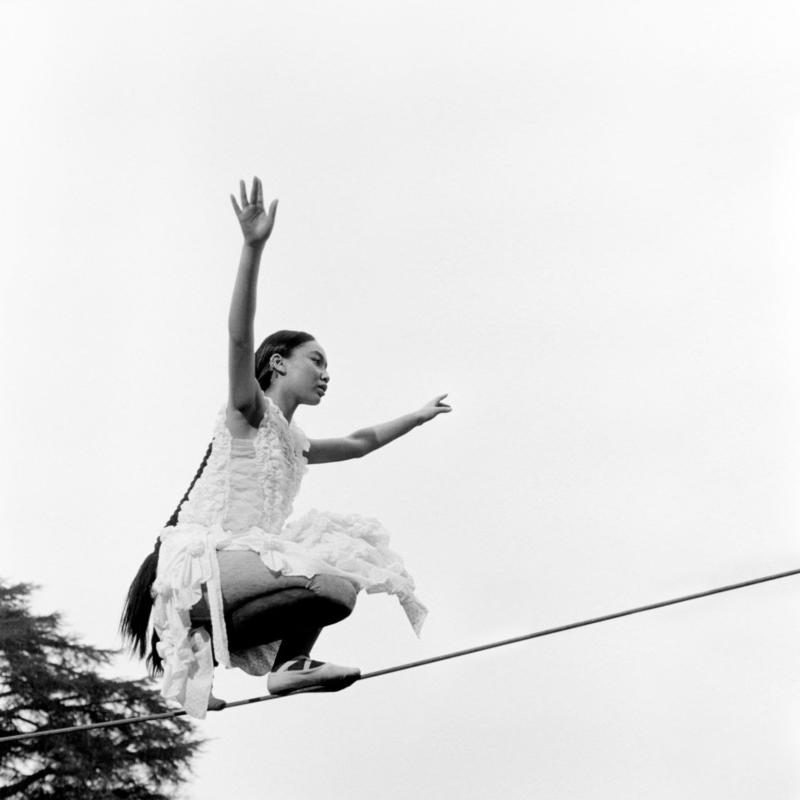 Capa do álbum One Foot In Front Of The Other. A imagem mostra uma mulher, com vestido de babados e cabelo preso, agachada em uma corda bamba, Ela usa sapatilhas de balé nos pés e tem os braços abertos. A imagem é em branco e preto e ao fundo vemos apenas o pedaço de uma copa de árvore no canto inferior esquerdo.