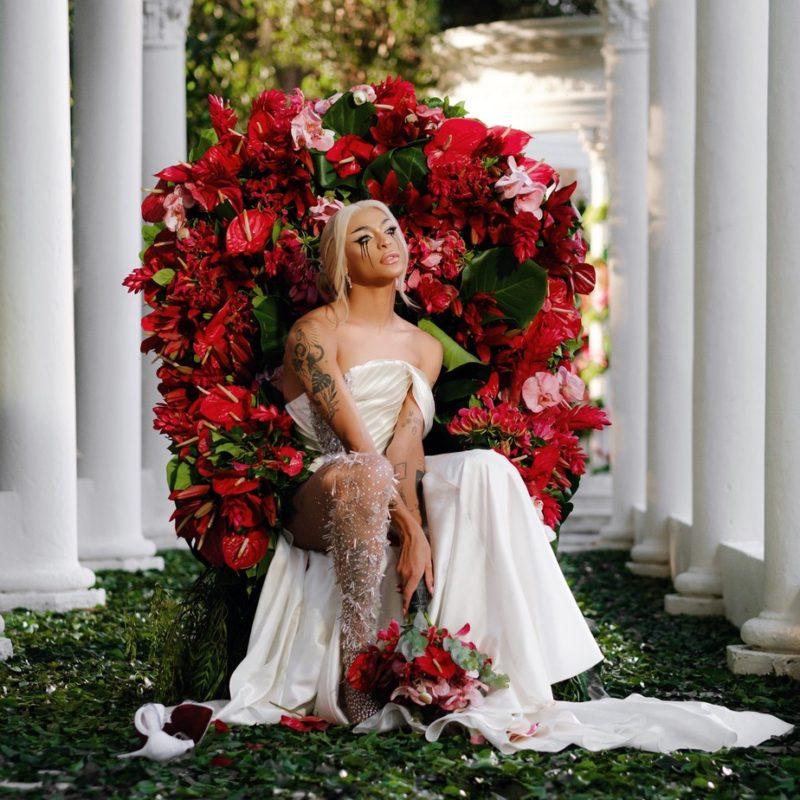 Cena do clipe de Ama Sofre Chora. Na imagem, Pabllo Vittar está sentada usando um vestido branco e longo de noiva, cabelo loiro amarrado segurando um buquê de flores e olhando para o lado com os olhos borrados escorrendo o lápis de olho. Em suas costas, uma coroa enorme de flores. No fundo, pilares brancos.