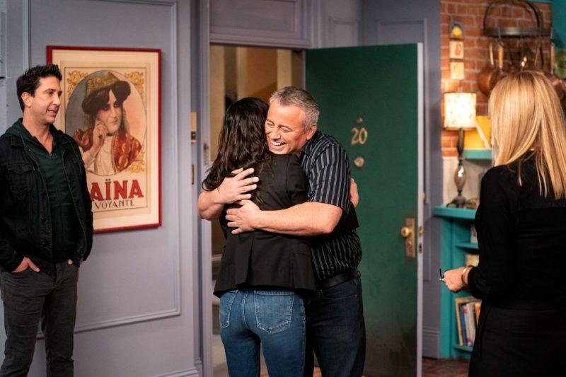 Cena de Friends The Reunion. À esquerda está David Schwimmer. Ele está em pé e com as mãos no bolso. Ao centro está Courteney Cox e Matt LeBlanc. Eles estão se abraçando. À esquerda está Lisa Kudrow de costas, olhando para Courteney e Matt. O fundo é uma parede lilás e há uma porta verde aberta.